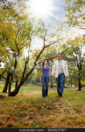 Park Couple Walk stock photo, A happy couple walking in the park - looking at the camera by Tyler Olson