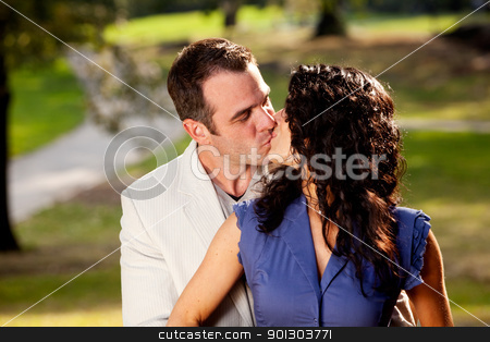 Happy Kiss stock photo, A couple in the park happy and kissing by Tyler Olson