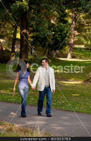 Couple Walk Park stock photo, A couple happy and walking in a park by Tyler Olson