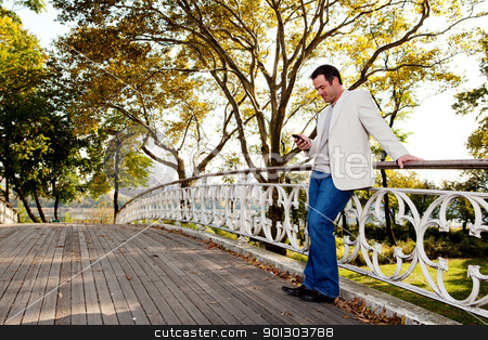 Cell Phone Park stock photo, A man checking his cell phone in a park by Tyler Olson