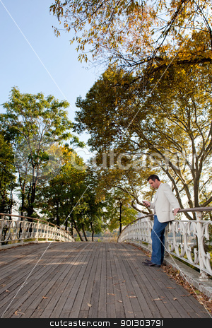 Cell Phone Man Park stock photo, A man checking his cell phone in a park by Tyler Olson