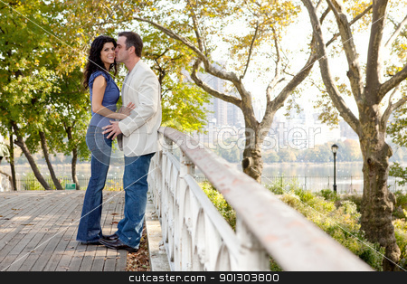 Kiss Park stock photo, A man kissing a woman in a park on a bridge by Tyler Olson