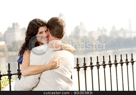 Hug Smile Woman stock photo, A woman hugging a man and looking at the camera with a smile by Tyler Olson