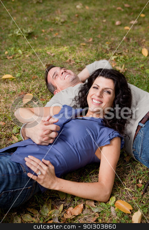Happy Park Couple stock photo, A happy couple relxing laying in the grass - sharp focus on the woman by Tyler Olson