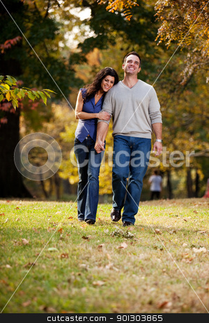 Walk Park Love stock photo, A happy couple walking in the park on grass by Tyler Olson