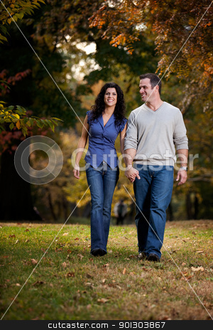 Happy Couple Walk stock photo, A happy couple walking in the park on grass by Tyler Olson