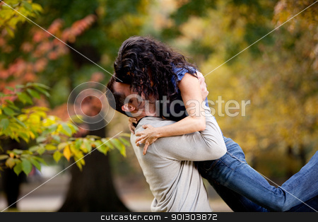 Bear Hug stock photo, A man giving a woman a big hug in a park by Tyler Olson