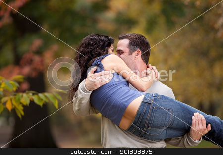 Healthy Relationship stock photo, A playful couple - man holding woman in the park by Tyler Olson