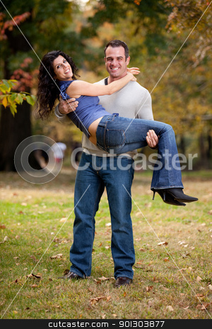 Happy Couple stock photo, A happy healthy couple in the park - Man holding the Woman by Tyler Olson