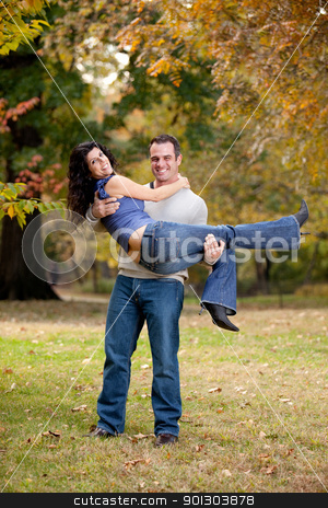 Healthy Relationship Couple stock photo, A happy healthy couple in the park - Man holding the Woman by Tyler Olson