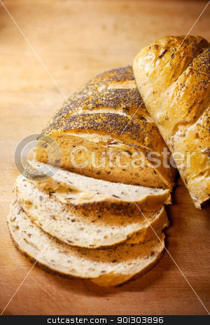Fresh Bread Slice stock photo, Fresh home-made onion and wild rice bread garnished with poppy seeds by Tyler Olson