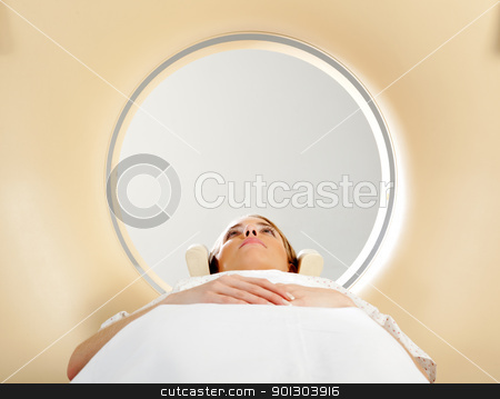 Woman taking CT Scan stock photo, A woman laying down with eyes open having a CT scan by Tyler Olson