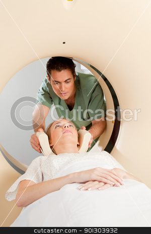 Patient in CT Scan stock photo, A young woman having a CT scan taken - Nurse getting things prepared by Tyler Olson