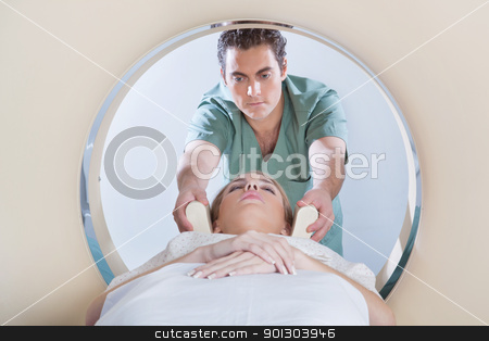 Young woman going through CT test stock photo, Nurse preparing young woman for CT scan test by Tyler Olson