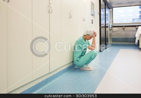 Upset surgeon sitting alone stock photo, Upset surgeon sitting alone after she failed an operation by Tyler Olson