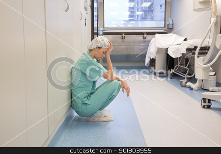 Tired Doctor in Hospital Hallway stock photo, Tired doctor sitting alone in hallway by Tyler Olson