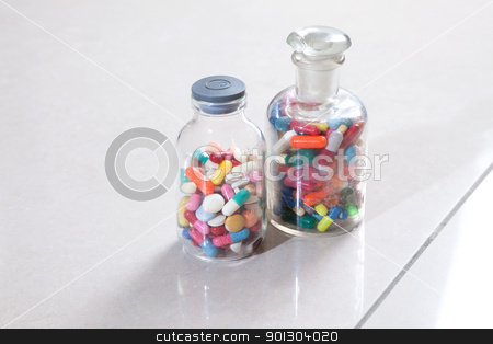 Bottle of medicine stock photo, Two bottles with tablets and capsules by Tyler Olson