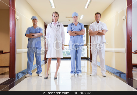 Team of doctor and nurse standing stock photo, Team of doctor and nurse standing in hallway of hospital by Tyler Olson