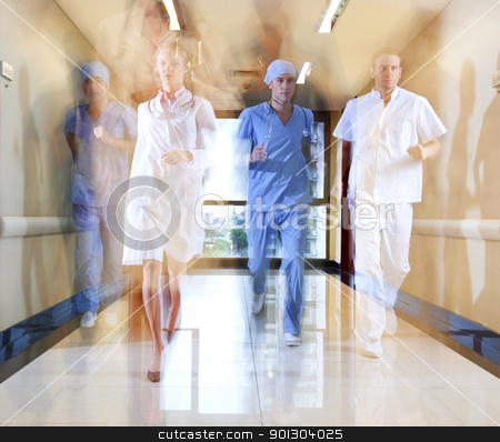 Team of doctor and nurse running stock photo, Team of doctor and nurse running in hallway of hospital by Tyler Olson