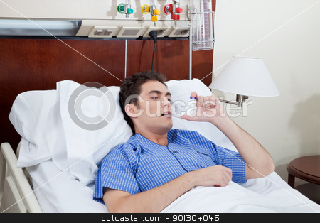 Patient using asthma inhaler stock photo, Asthmatic male patient on bed using asthma inhaler by Tyler Olson