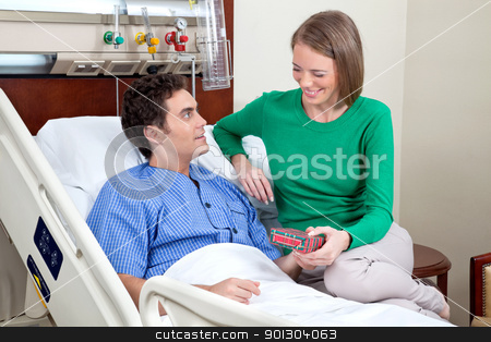 Wife giving present to husband stock photo, Wife giving present to her husband in hospital by Tyler Olson