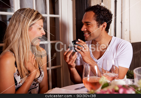 Give Ring Gift stock photo, A man giving a ring as a gift to a female in an outdoor cafe by Tyler Olson