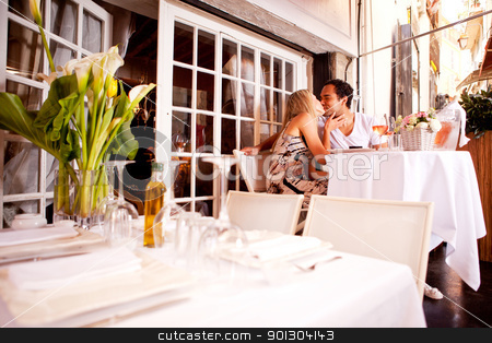 Romantic Couple in Restaurant stock photo, A romatic couple kissing in an outdoor restaurant by Tyler Olson