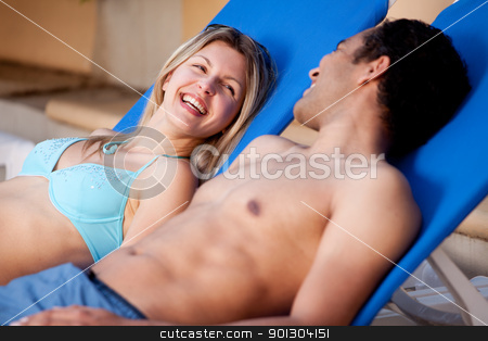 Happy Beach Couple stock photo, A happy couple on pool side chairs having fun by Tyler Olson