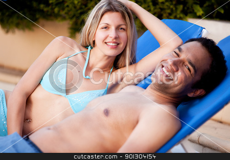 Happy Beach Couple stock photo, A happy couple on beach chairs, looking at the camera by Tyler Olson