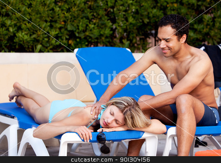Luxury Back Massage stock photo, A woman receiving a back massage on a pool chair by Tyler Olson