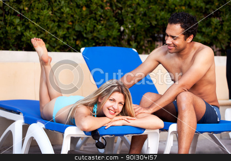 Back Massage Beach stock photo, A man giving a back massage to a woman on a beach chair by Tyler Olson