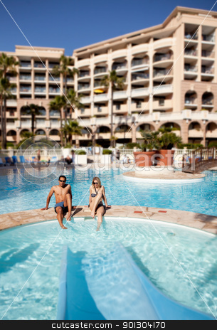 Hotel Pool stock photo, A man and woman enjoying a hotel pool with waterslide by Tyler Olson