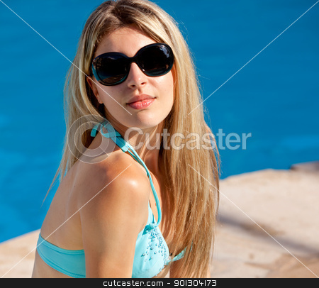 Pool Model with Sunglasses stock photo, A model sitting beside a pool with sunglasses on by Tyler Olson