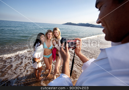 Picture of Friends stock photo, A man taking a photo of three women at the ocean. by Tyler Olson