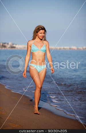 Woman on Beach stock photo, A woman walking along the water on an ocean beach by Tyler Olson