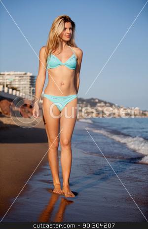 Woman Walking on Beach stock photo, A beautiful woman walking on a beach seaside by Tyler Olson