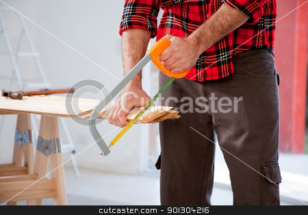 Cut Wood Handsaw stock photo, A detail of a man cutting wood with a small hand saw by Tyler Olson