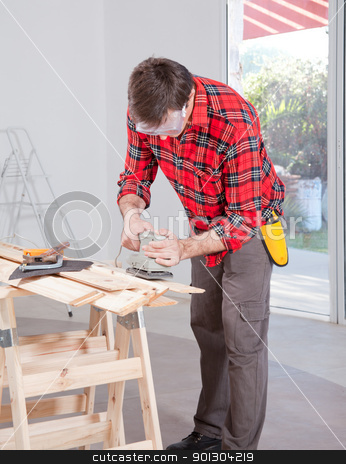 Man Using Electric Hand Sander stock photo, A man at home using an electric hand sander with safety goggles by Tyler Olson