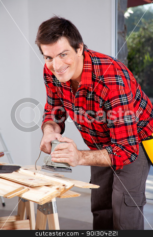 Man with Electric Hand Sander stock photo, A man looking at the camera holding an electric sander by Tyler Olson