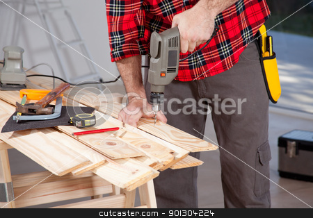 Electric Hand Drill stock photo, A male using an electric hand drill on a plank by Tyler Olson
