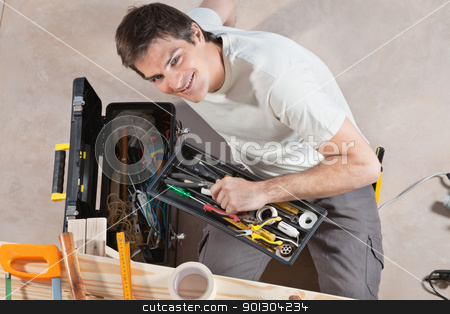 Man holding tool box stock photo, Portrait of smiling young man holding his tool box by Tyler Olson