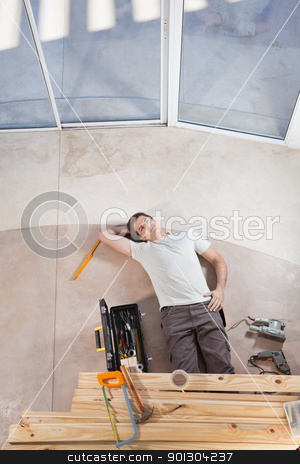 Home Improvement stock photo, Man laying on ground with home improvement tools by Tyler Olson