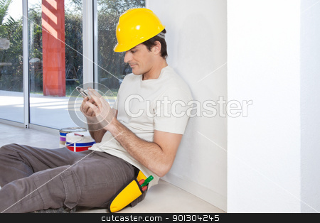Construction worker with phone stock photo, Construction worker looking in cellphone while sitting by Tyler Olson