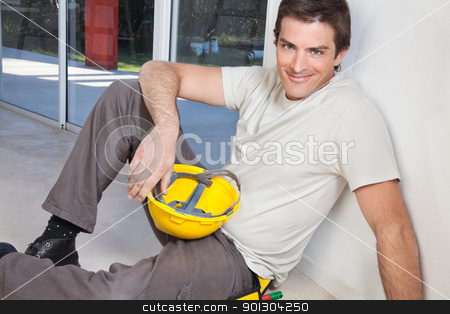 Portrait of young smiling man stock photo, Portrait of young man sitting with construction helmet by Tyler Olson