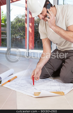 Architect working on blueprint stock photo, Architect working on blueprint and talking on cellphone by Tyler Olson