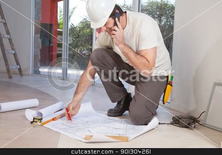 Construction worker working on blueprint stock photo, Construction worker working on blueprint and talking on cellphone by Tyler Olson