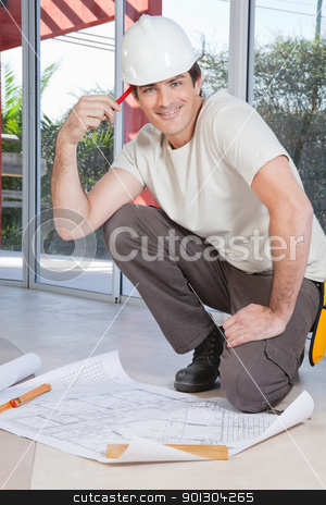 Smart young construction worker stock photo, Smart young construction worker smiling with blueprint on floor by Tyler Olson