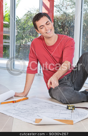 Engineer pointing at blueprint stock photo, Young engineer smiling and pointing at blueprint by Tyler Olson