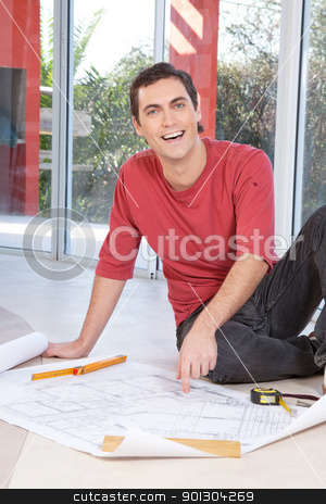 Portrait of happy smiling man stock photo, Portrait of happy smiling man pointing at blueprint of paperwork by Tyler Olson