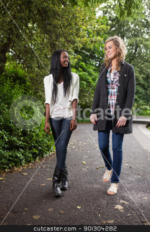 Women enjoying walk in park stock photo, Two young women enjoying walk in the park by Tyler Olson